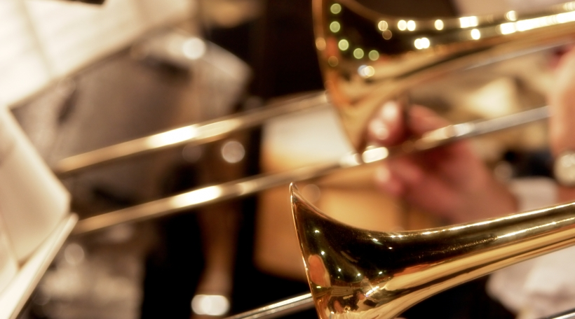 trombones playing live in a big band (shallow focus).