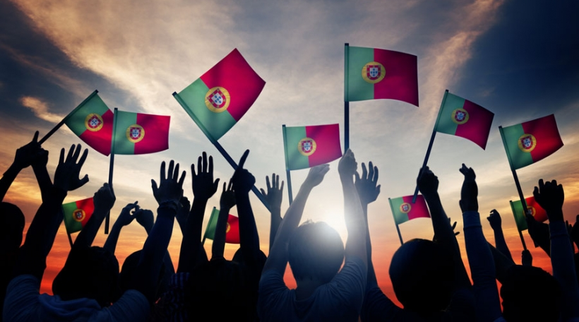 Group of People Waving Portuguese Flags in Back Lit Concept