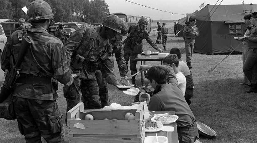 Members of the 1st Battalion, 28th Infantry Division, receive food served by Luxembourg Army Reservists.  The men have just arrived aboard a C-141 Starlifter aircraft and are en route to Karlsruhe, West Germany, to participate in REFORGER '82.