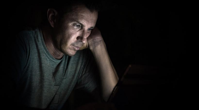 Mann kuckt op Laptop-Schierm