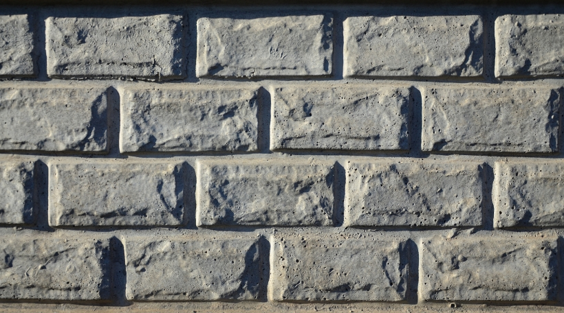 Stone fence texture - building feature. Texture of concrete fence with relief and texture like a stone wall