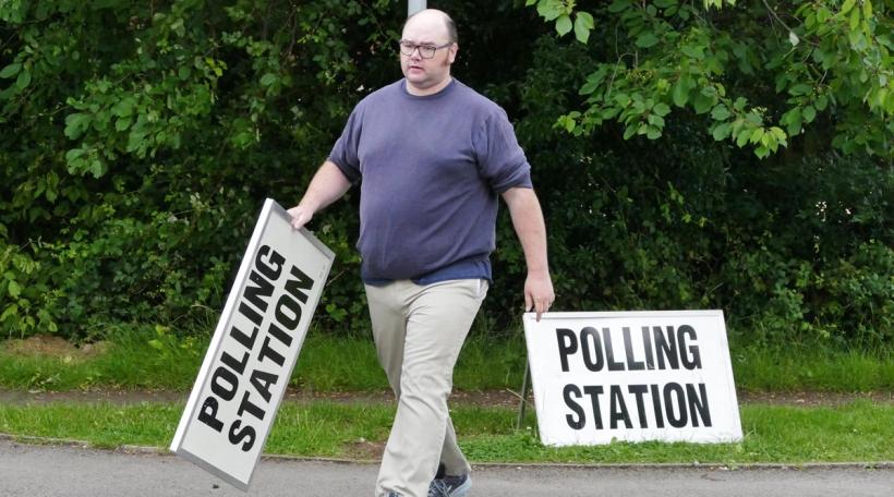 Wahlen a Groussbritanien. Een Här zu Reading stellt Schëlter virum Wahlbureau op.