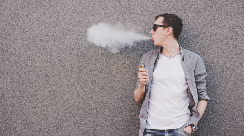 Jonke Mann fëmmt elektronesch Zigarett