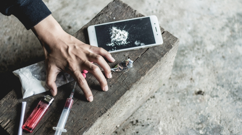 Young human hand trying to reach drugs, The concept of crime and drug addiction. 26 June, International Day Against Drug Abuse and Illicit Trafficking