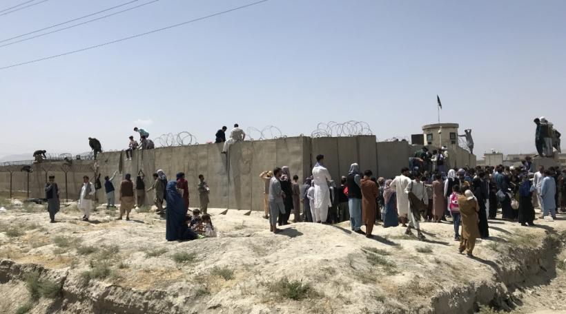 Leit probéieren iwwer d'Mauere vum Hamid-Karzai-Flughafen ze klammen